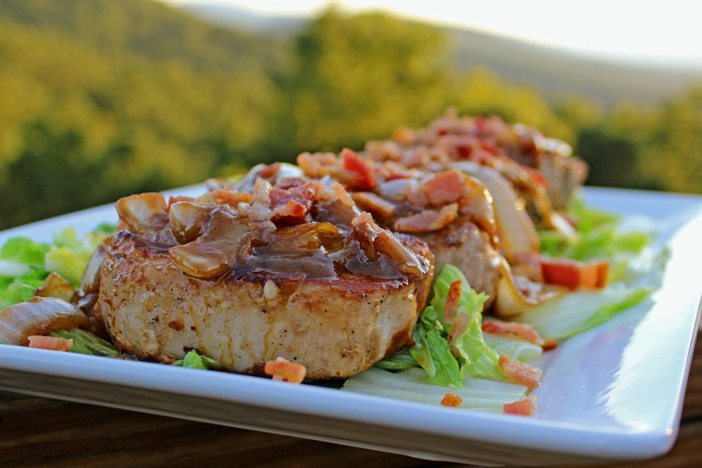 delectable pan-seared pork chops with dijon bacon vinaigrette on a platter with cabbage and mountain view