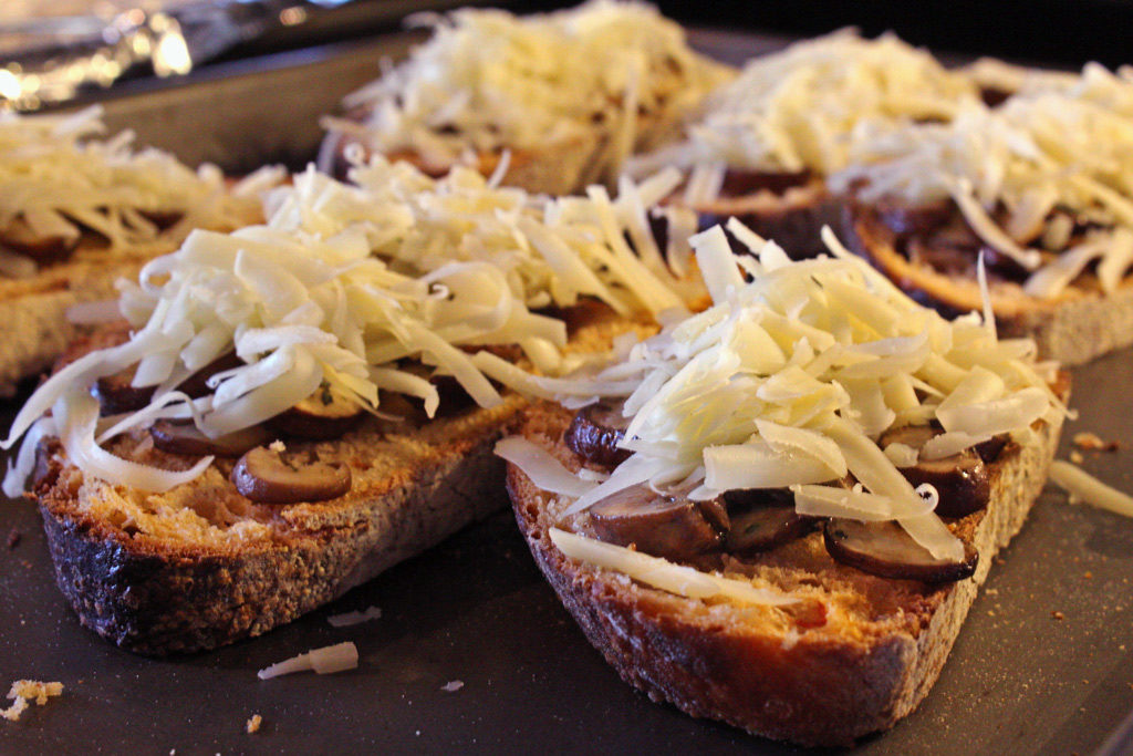 shredded cheese on bread and mushrooms