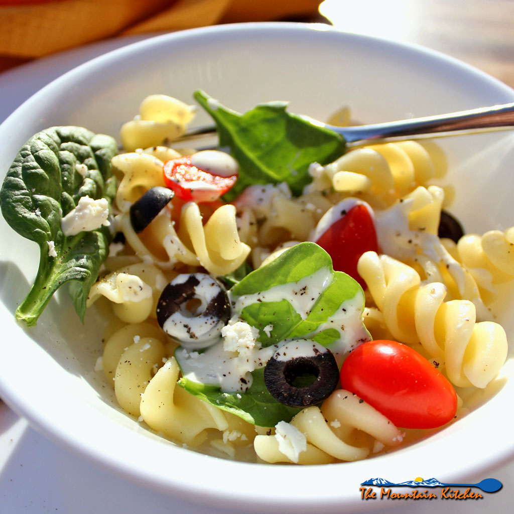 This easy to make Mediterranean pasta salad is refreshing, satisfying, hearty, and filled with rich flavors and textures. Pasta tossed with fresh tomatoes, black olives, healthy spinach and feta cheese, drizzled with dressing. It's simple and and blissfully delicious! | TheMountainKitchen.com