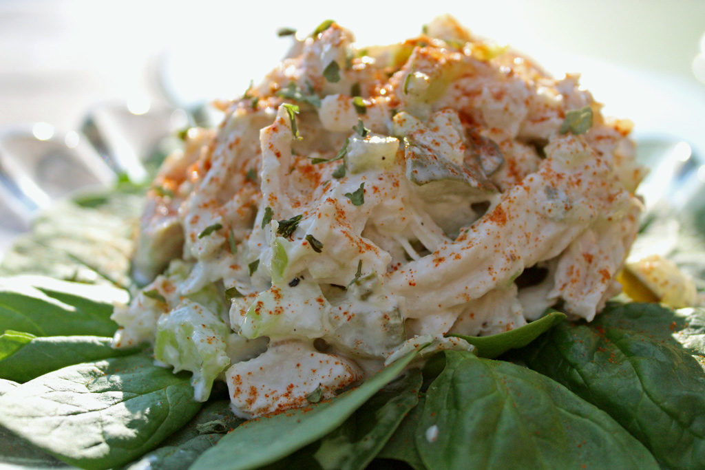 Chicken salad sitting on a bed of fresh spinach.