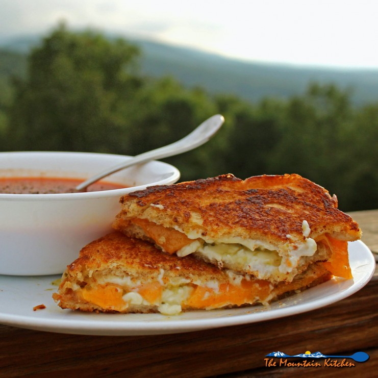 Jalapeno pepper jelly grilled cheese sandwich and bowl of soup on plate with mountain view