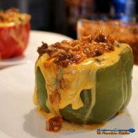 These tender stuffed bell peppers are filled with cheese, Spanish seasoned beef and rice, topped with even more cheese. A classic comfort food favorite! | TheMountainKitchen.com