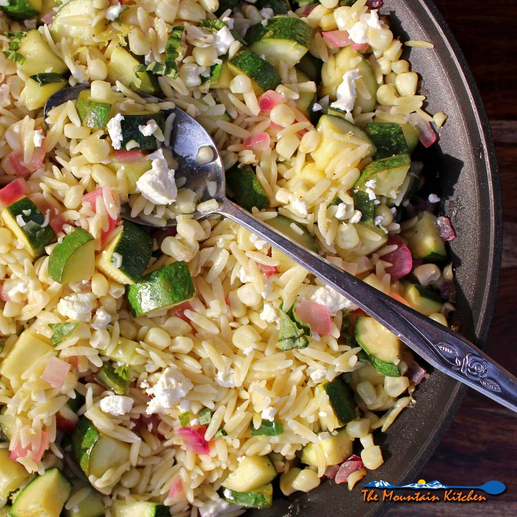 Summer is bursting with flavor in this corn zucchini orzo salad. Seasonal vegetables combine with orzo and feta for a quick pasta salad!