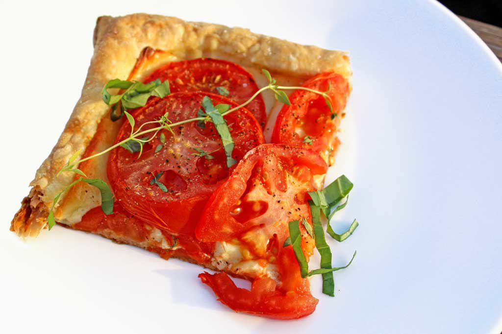 Roasted tomato cheese tart: puff pastry, ripe tomatoes Dijon mustard, smoked Gruyere cheese, simply seasoned with fresh thyme, fresh basil, salt and pepper.