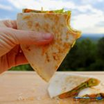holding wedge of squash blossom quesadilla