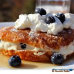 Christmas brunch? Try this stuffed croissant French toast! Buttery, flaky croissants stuffed with blueberry cream cheese, drenched in warm maple syrup.