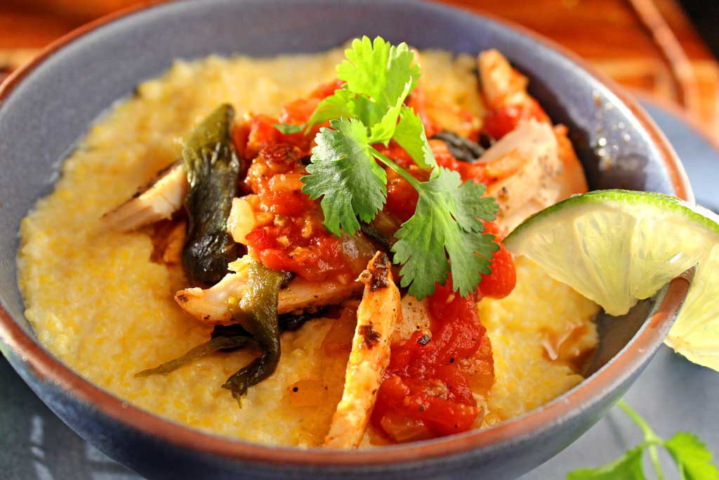 Spicy chicken poblano stew with polenta puts a Mexican spin on Italian food. With only 389 calories per serving, this hearty weeknight dish is made of shredded chicken, stewed with smoky poblanos, and onions in agarlicky tomato sauce spiced up with adobo sauce, served over creamy sweet porridge of polenta. | TheMountainKitchen.com