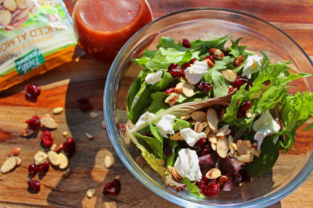 Ready in just 10 minutes, this gorgeous Cranberry-Almond Salad has many delicious and bright flavors, like spring salad greens, sweet cranberries, crunchy almonds and tangy goat cheese drizzled with a delicious homemade raspberry vinaigrette. This simple salad is one you will want to enjoy all year long! | TheMountainKitchen.com