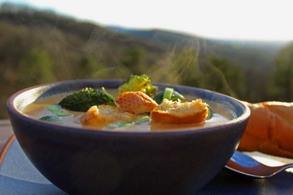 steaming bowl of carrot-ginger soup with mountain view