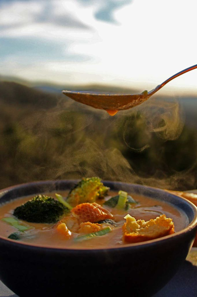 steaming spoonful of carrot-ginger soup with mountain view