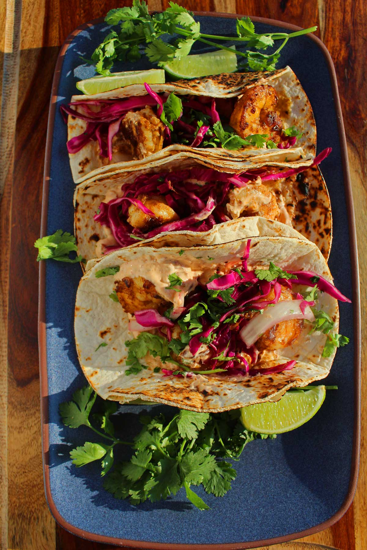 Warm garlicky shrimp, fresh sweet and tangy red cabbage slaw, with smoky and spicy sour cream, intensely flavor these easy shrimp tacos. You'll love em!