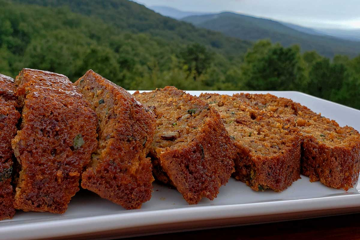Slices of zucchini bread on a platter with the mountains in the background.
