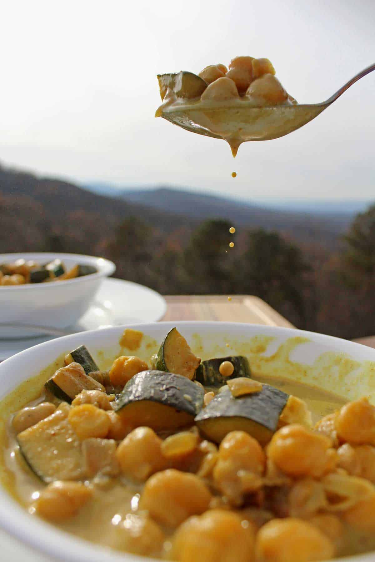 A dripping spoonful of stew with the mountains in the background.