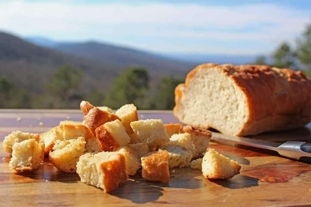 A loaf of bread with homemade croutons on a board with the mountains in the background.