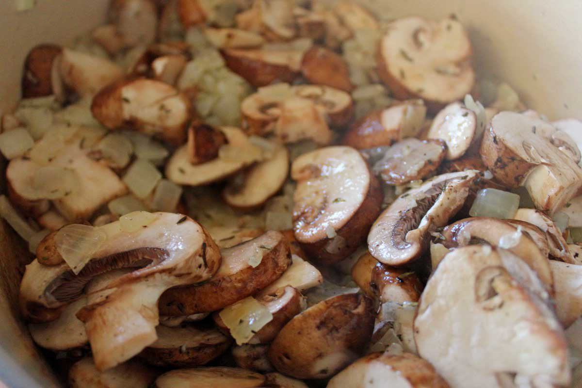 mushrooms and onions cooking in a pot