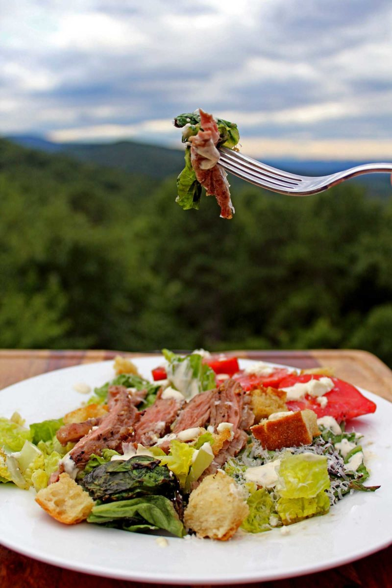 a bite of grilled steak Caesar salad with mountain view
