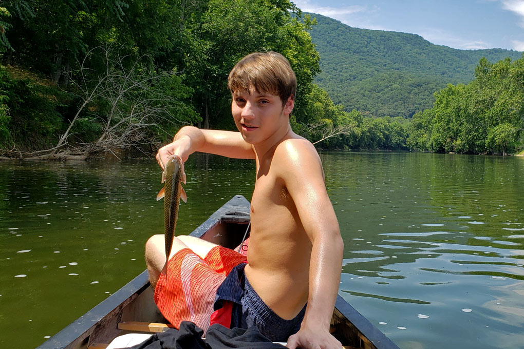 seth in canoe with fish