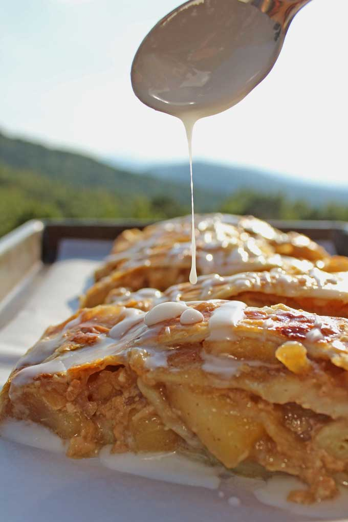 drizzling vanilla glaze onto the caramel apple strudel with mountain view in background