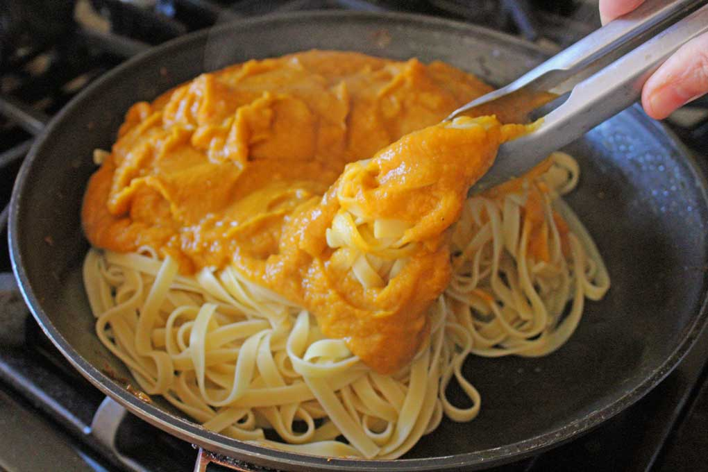tossing pasta with butternut squash sauce
