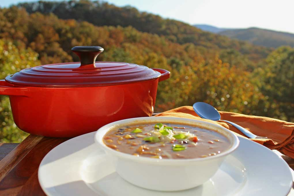bowl of chili and dutch oven with mountain view