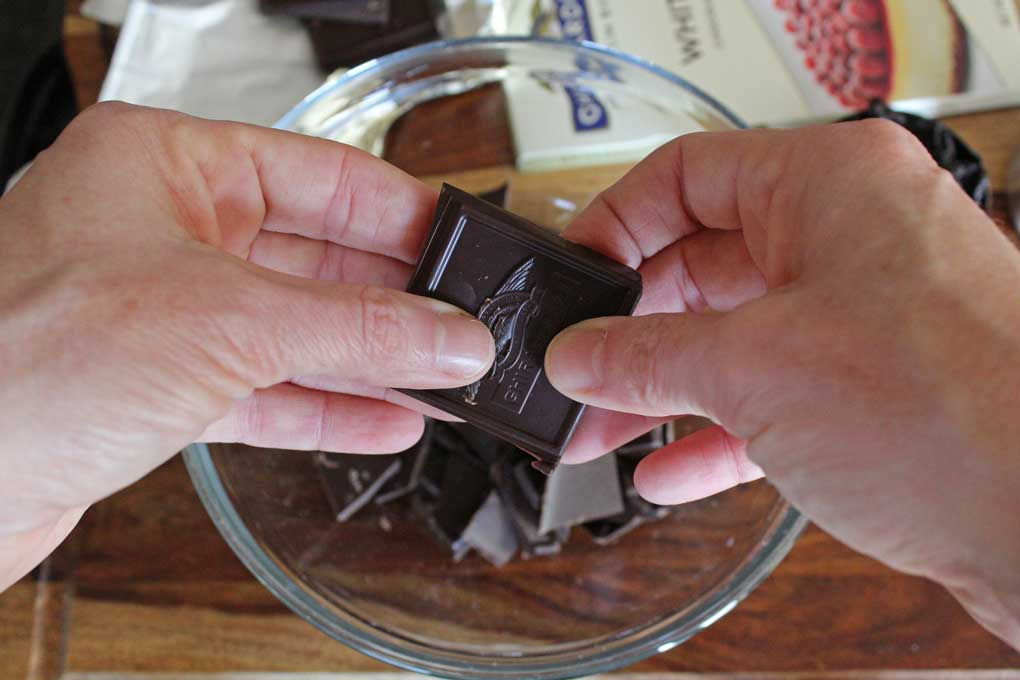 breaking chocolate into bowl
