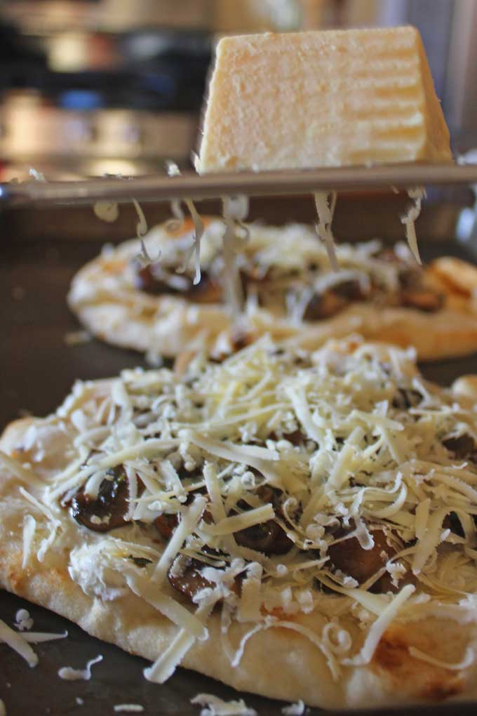 adding shredded cheese on top of mushrooms