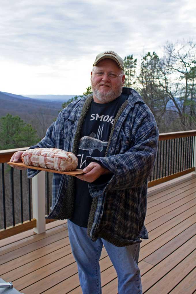 David holding meatloaf on cedar plank