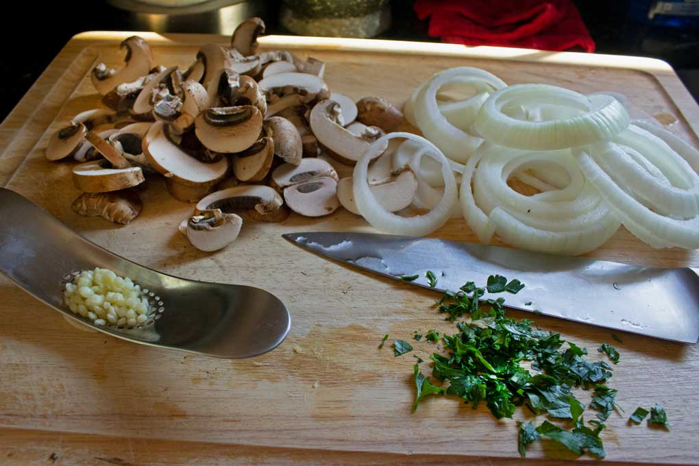 mushrooms, onion, parsley and garlic chopped on cutting board