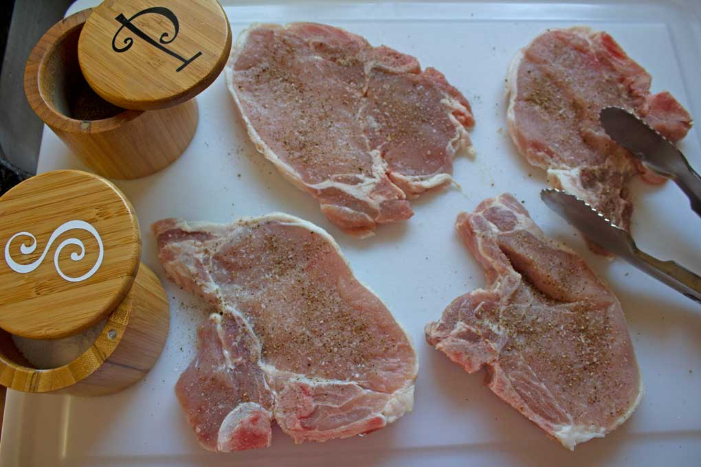 raw pork chops seasoned with salt and pepper