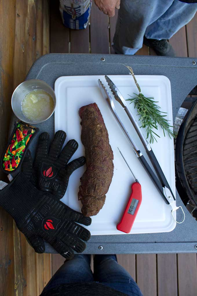 smoked meat on cutter board with tongs, herb brush, grill gloves, instant-read thermometer and pot of garlic butter