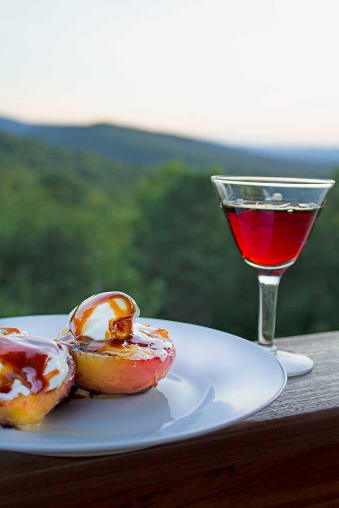 Grilled peaches and plums with yogurt and caramel sauce is a healthy way to lighten up dessert this summer. Try this grilled dessert at your next cookout!