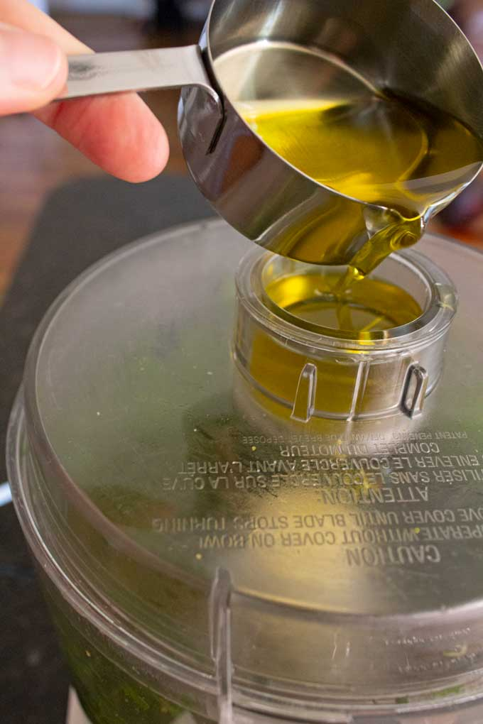 pouring olive oil into drizzle spout of food processor