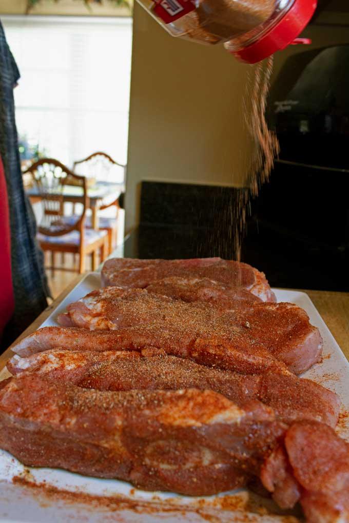 sprinkling rub onto pork ribs