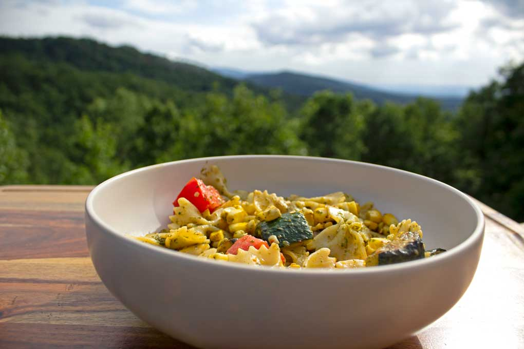 pesto pasta with summer vegetables in bowl with mountain view