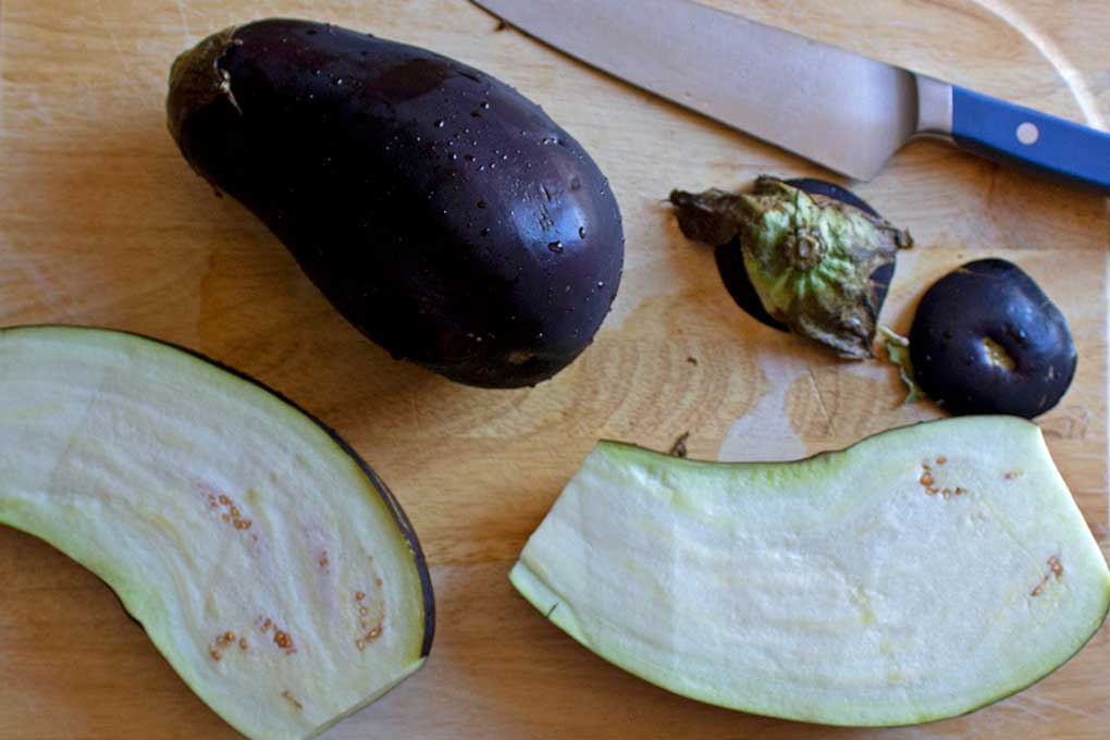 sliced eggplant on cutting board for Mediterranean quinoa-stuffed eggplant