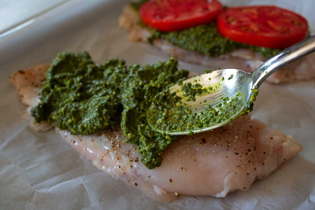 spreading pesto onto chicken with spoon