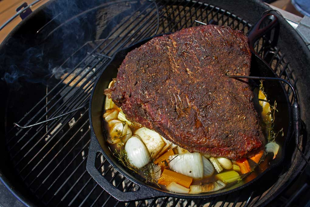 smoked brisket in cast iron pan with vegetables