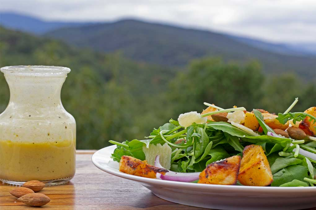 butternut squash arugula salad with mountain view and bottle of dressing