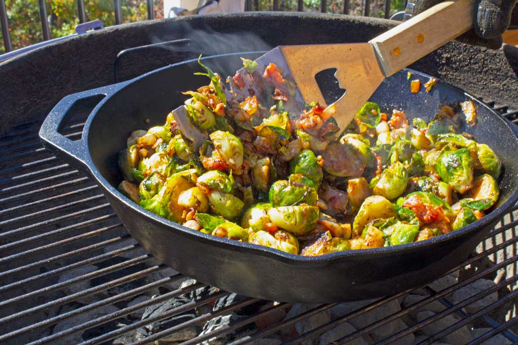 spatula stirring brussels sprouts in pan on grill