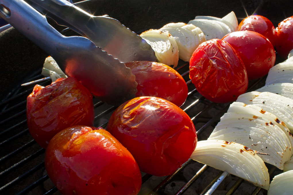 tossing the tomatoes for grilled tomato soup with tongs