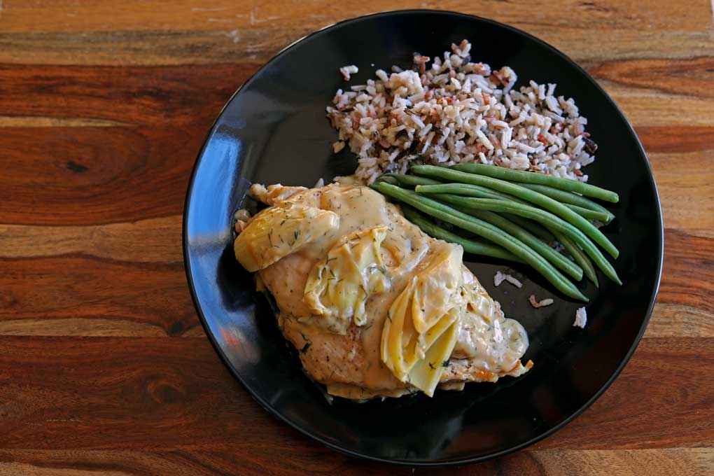 chicken and artichokes with lemon dill cream sauce on plate with rice and green beans